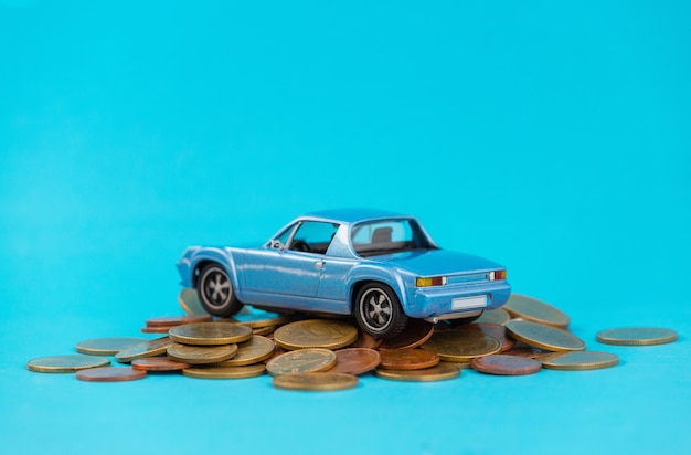 Модель синей автостоянки на стеке золотых монет