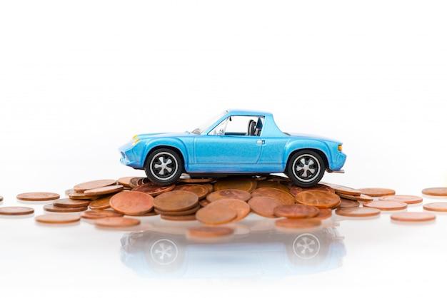 Модельная голубая автостоянка на монетках стога золотых изолированных на белой предпосылке.