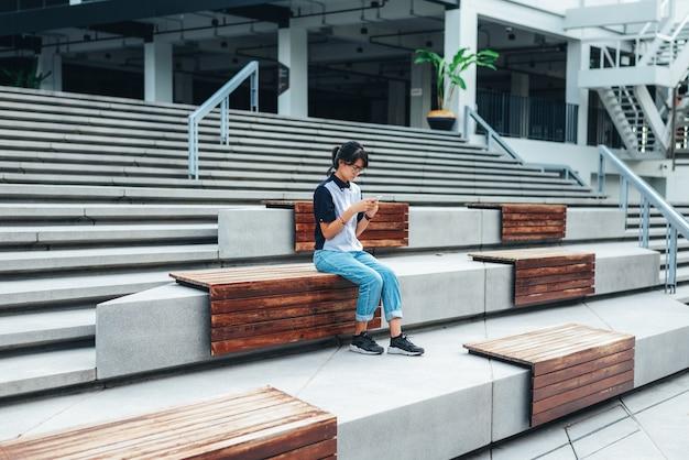 階段の上に座っているアジアの女性は、スマートフォンの読み取りテキストメッセージを使用し、写真を撮る