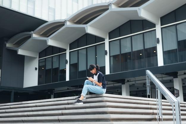 Азиатская женщина, сидящая на лестнице, использует смартфон, читает текстовое сообщение и делает фотографии