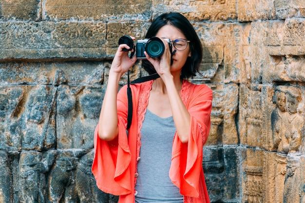 アジアの女性一人旅行者がインドネシア、ジャワのボロブドゥール寺院で写真古代建築物を撮る