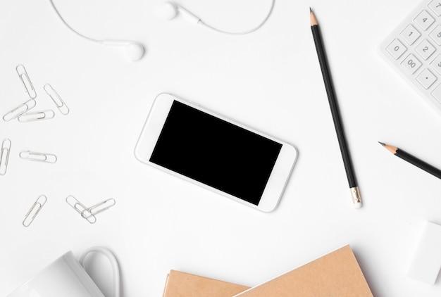 事務机の上のオフィスアクセサリーと空白のスマートフォンディスプレイのフラットレイアウト