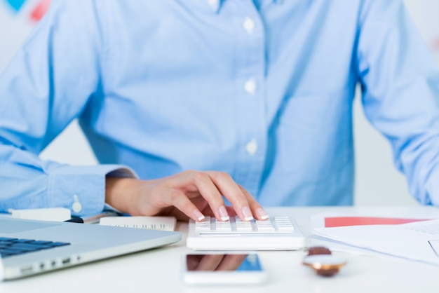 ワークスペースをオフィスの机の上の電卓を使用して実業家の手