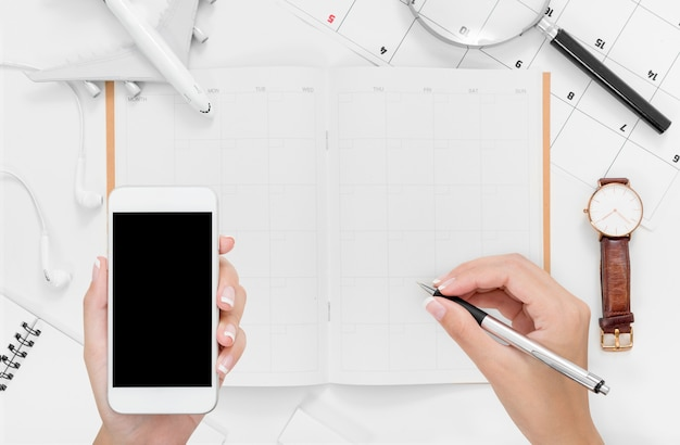 スマートフォンを使用して、空白スペースで旅行の旅程計画に書いて女性の手のフラットレイアウト