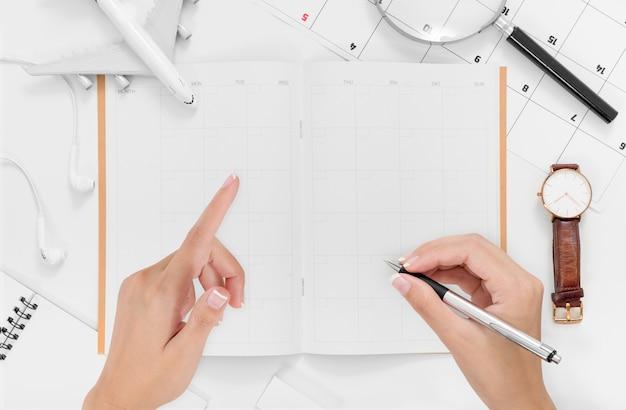 空白の旅程計画に書いている女性の手のフラットレイアウト