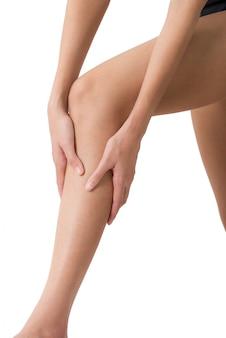 白で隔離される痛みの分野でのすねとふくらはぎのマッサージで彼女の足を保持している女性
