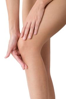 白で隔離される痛みの分野で膝をマッサージで彼女の足を保持している女性