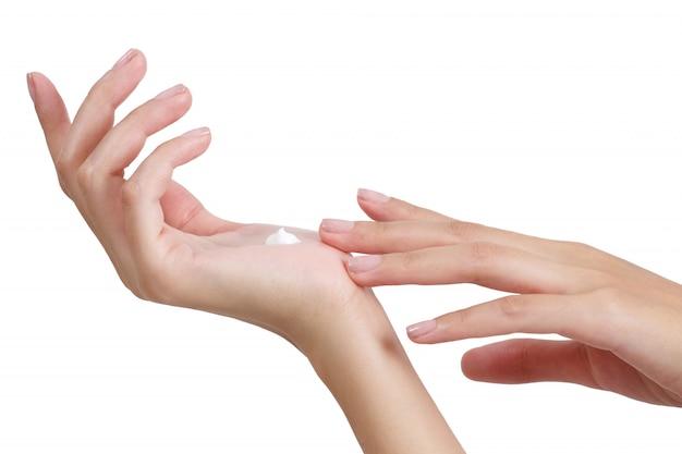 美しい女性の手の白い背景で隔離の手に適用ローションでリラックス