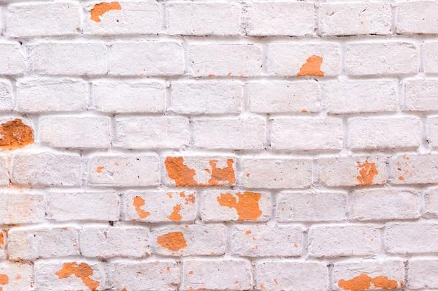 Белая кирпичная стена с текстурой и фоном оранжевого цвета