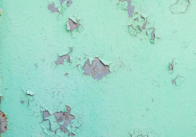 Трещины и шелушение краски зеленого цвета на стали с ржавой текстурой и фоном
