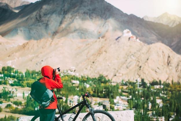 Фотограф ждет свет, фотографируя величественные гималаи на велосипеде
