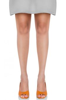 立っている女性のポーズを白で隔離される正面プロファイルと革分厚いハイヒールのファッション靴を履いて