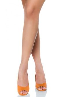 女性の足を組んで立ってポーズを白で隔離される正面プロファイルと革分厚いハイヒールのファッション靴