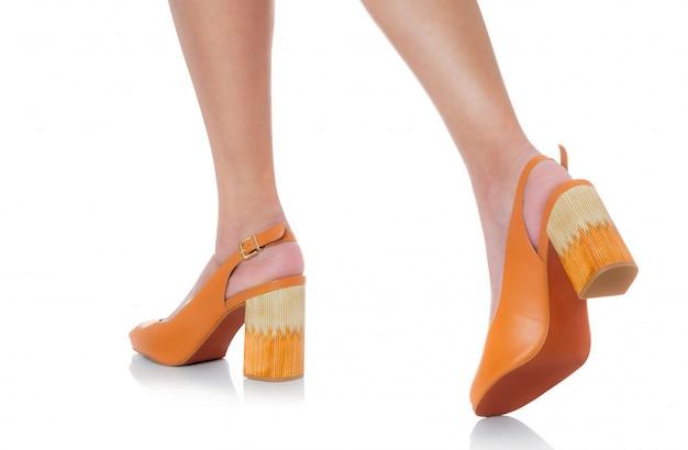 白で隔離される裏面ビュープロファイルでステッピング革分厚いハイヒールファッション靴を履いている女性