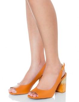サイドビュープロファイルで革の分厚いハイヒールファッション靴を着て立っている女性