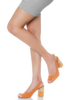 レザーチャンキーハイヒールファッション靴ポーズを着ている女性は、フロントサイドビュープロファイルで彼女の足を持ち上げる
