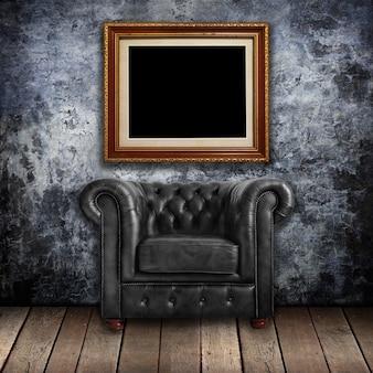 壁に古典的な黒い革張りのアームチェア