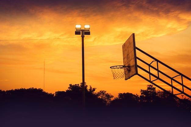 日の出の朝の劇的な空と屋外のバスケットボールコートのシルエット