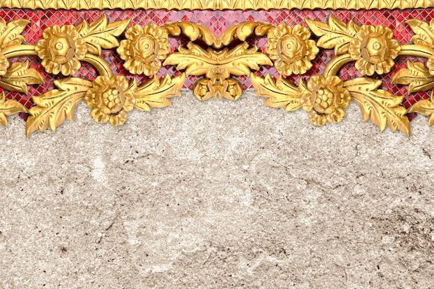 セメントの壁に刻まれた金の花のパターン