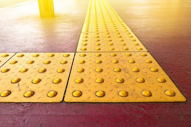 日本のタイル路上の盲目の障害者のための粗い黄色の点触覚舗装、失明者のための通路。