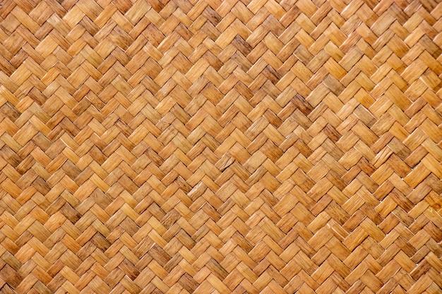 茶色の編まれたリードマットテクスチャ背景、タイの人々によって作られたかご細工のパターン。