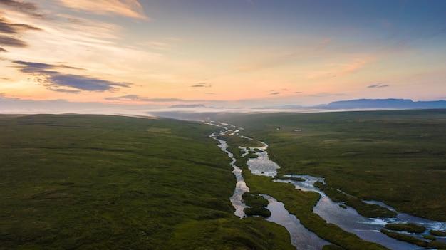 空撮アイスランド、夏の朝の牧草地と山の美しい風景