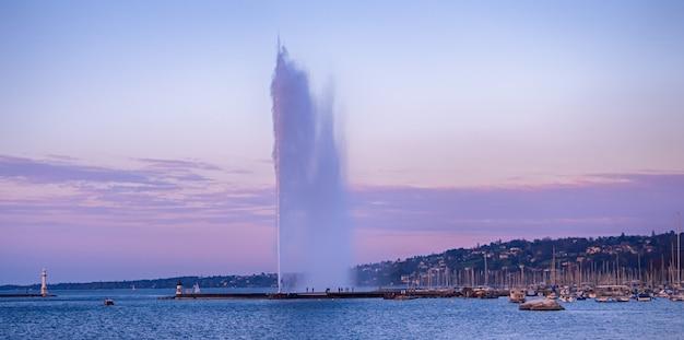 スイスのジュネーブの美しい港地区で有名な噴水の噴水のある歴史的なジュネーブスカイラインの美しい景色
