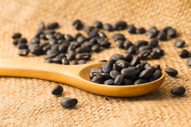 Крупным планом черная фасоль с деревянной ложкой
