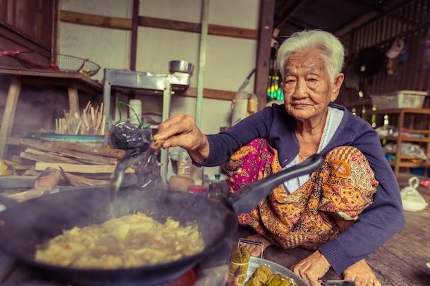 アジアのシニア女性シェフ、タイの伝統的な台所で調理します。