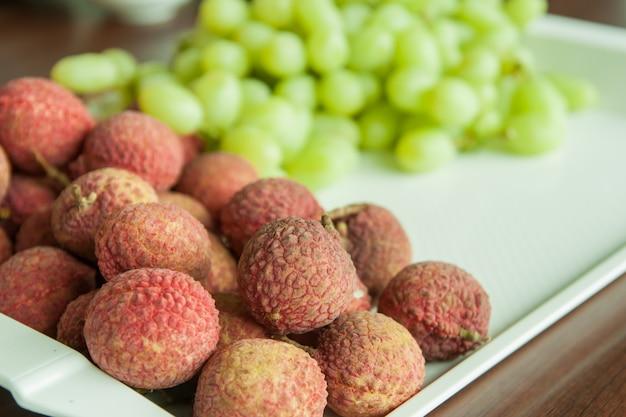 Свежий личи и виноград на подносе