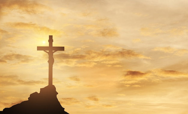 Силуэт иисуса и крест над закатом на вершине горы