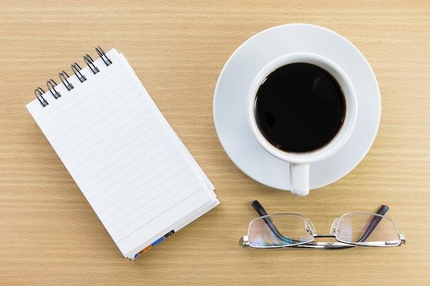 コーヒーとメモ帳の木のテーブル