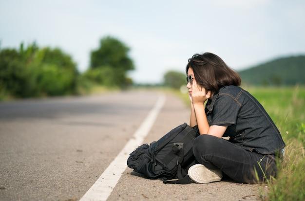 田舎の道に沿ってヒッチハイクのバックパックと座っている女性