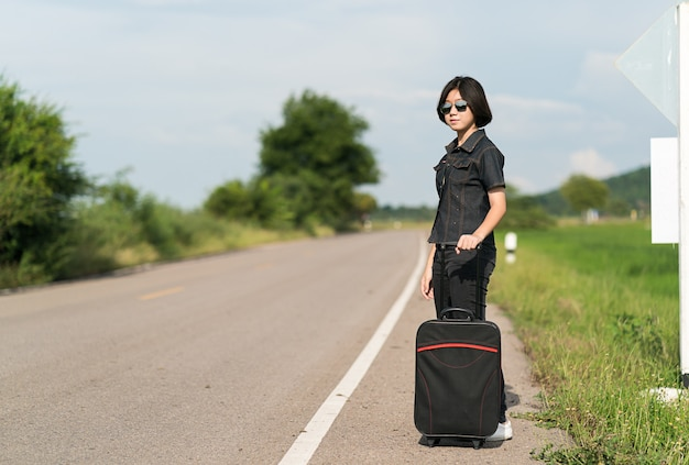 道路に沿ってヒッチハイクの荷物を持つ女性