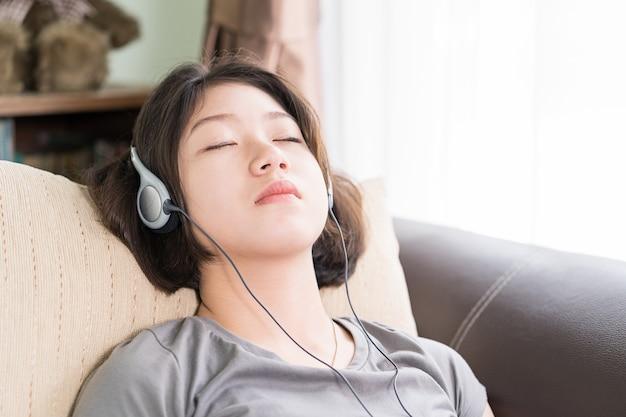 若い女性が携帯電話から音楽を聴く