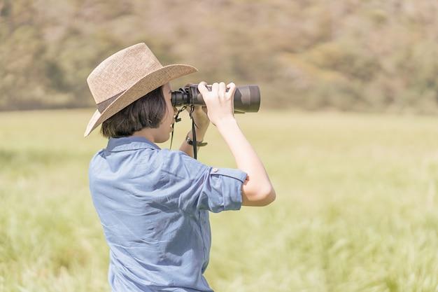 女性は帽子を着用し、芝生のフィールドで双眼鏡を保持