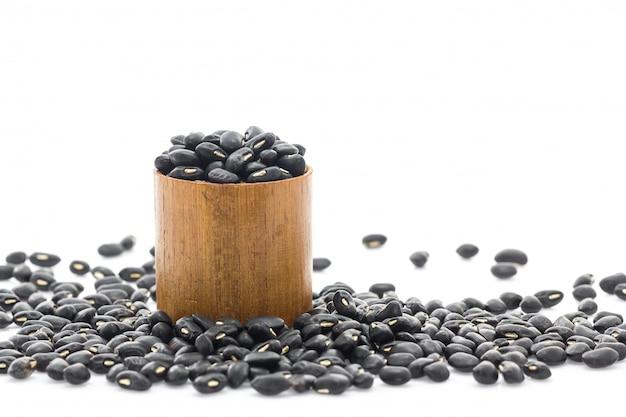 Черные бобы в деревянной чашке