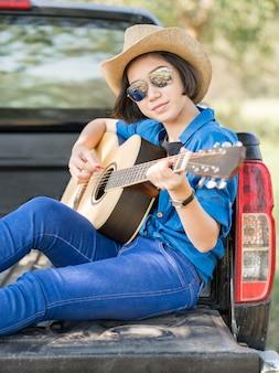 女性は帽子をかぶって、ピックアップトラックでギターを弾く