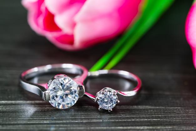 黒い背景にチューリップの花とダイヤモンドの結婚指輪