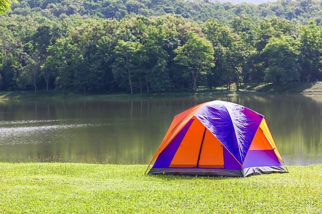 Туристическая купольная палатка в лесу на берегу озера