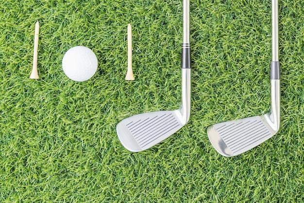 ゴルフクラブと緑の芝生の上のゴルフボール