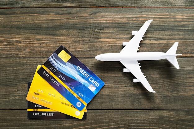 木製の机の上のクレジットカードと飛行機モデル