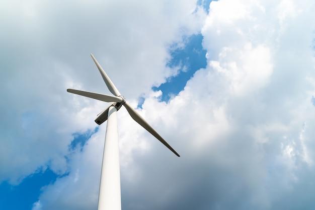 曇りの青い空を背景に風力タービン