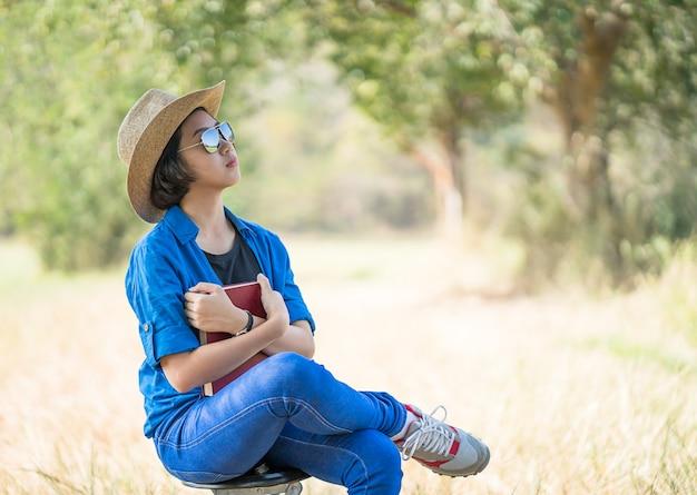 女性は帽子を着用し、椅子で本を読んで
