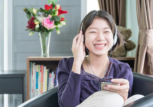 リビングルームで音楽を聴く若いアジア女性の短い髪