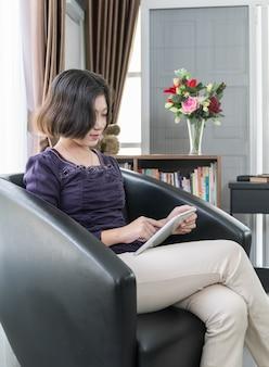 若いアジア女性の短い髪は、リビングルームで携帯電話を使用します。