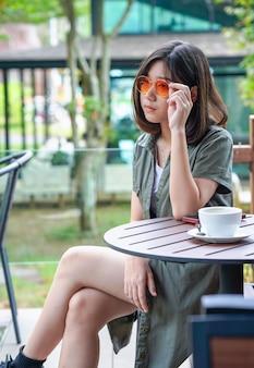 カフェのテラスに座っている女性