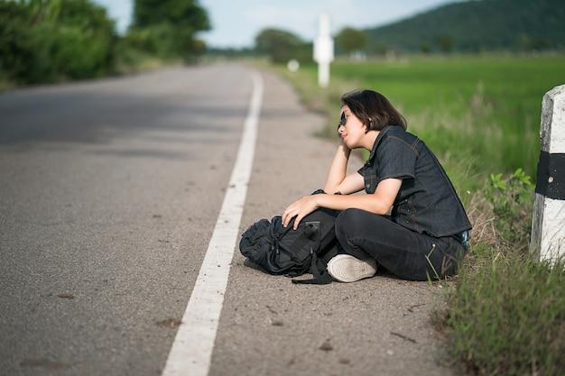 田舎の道に沿ってヒッチハイクのバックパックと女性座る