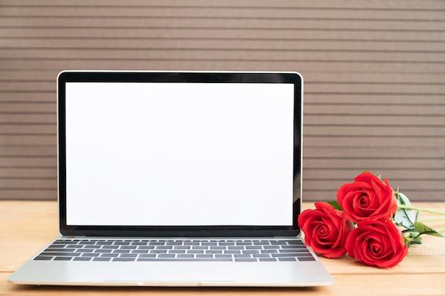 木の上の赤いバラとラップトップのモックアップ