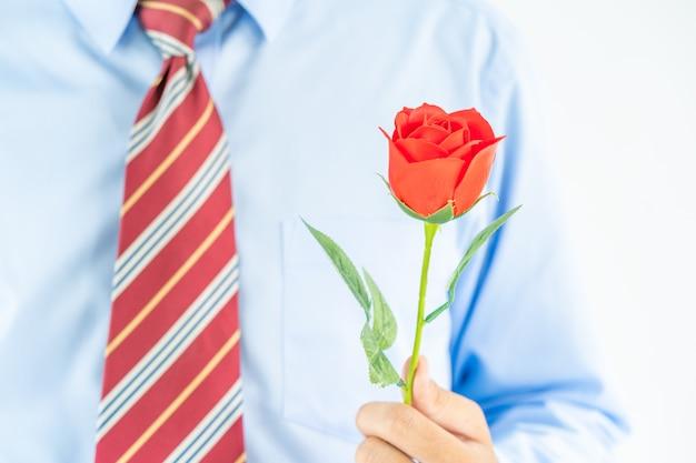 白地に赤いバラを持って男